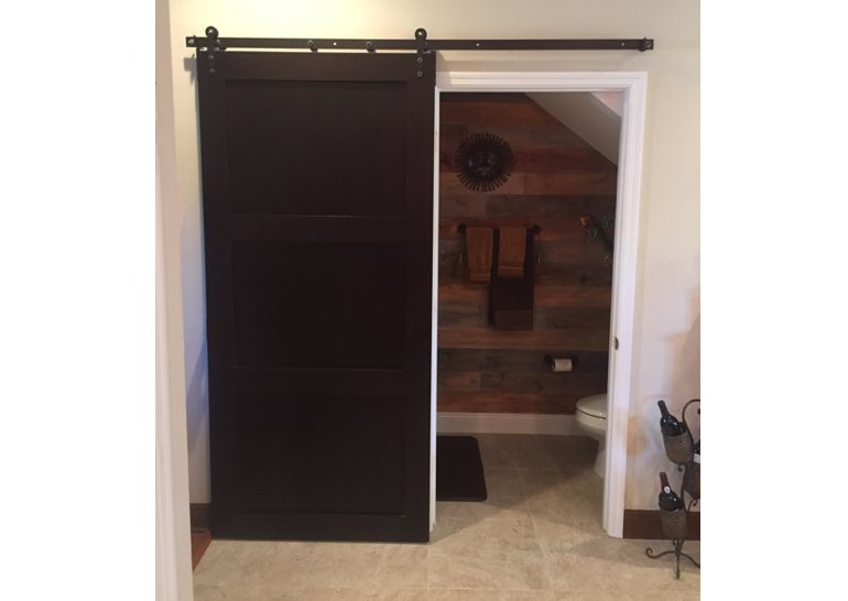 Brown sliding barn door covering bathroom entry 🚪