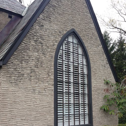 Exterior facade of stone home with plantation shutters