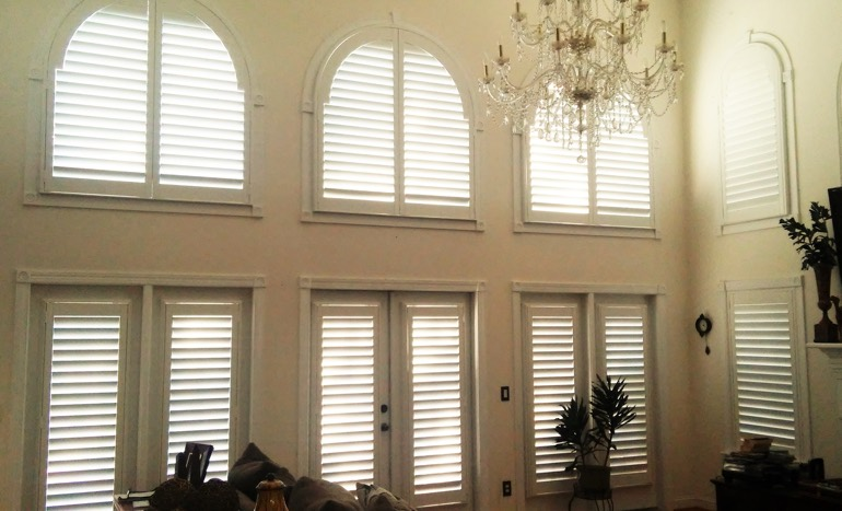 Family room in two-story Jacksonville house with plantation shutters on high windows.