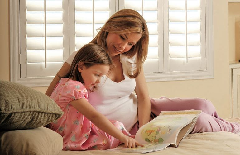 Mom and girl reading on bed with shuttered windows.