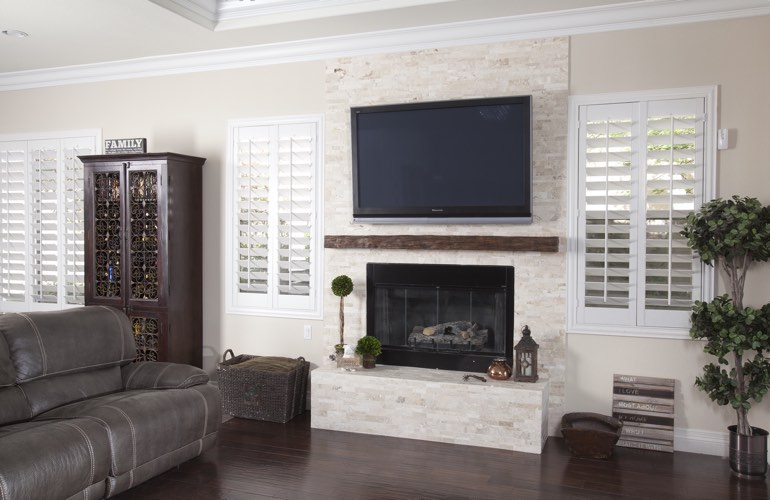 White plantation shutters in a Jacksonville living room with dark hardwood floors.