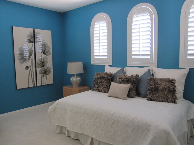 Bedroom with white plantation shutters.