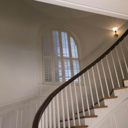White plantation shutters decorating rounded window located in round stairwell.