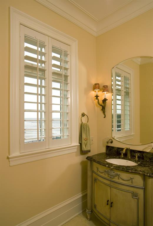 Plantation shutters in a light bathroom give a view of the ocean