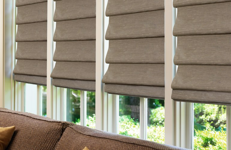 Decorative Roman shades in brown in sunroom window