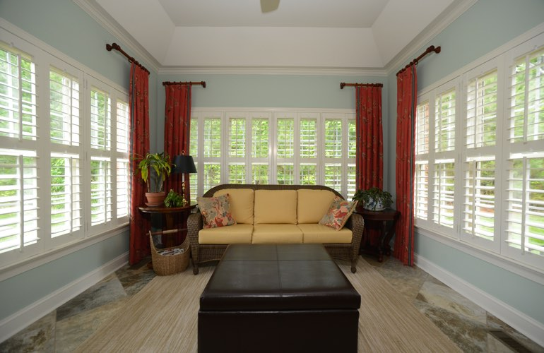 White plantation shutters covering windows in a sunroom