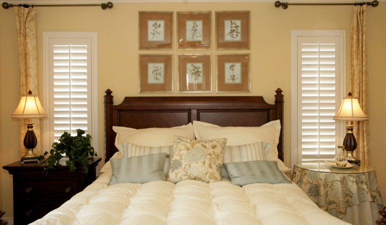 Tall plantation shutters framing bed in a bedroom in Jacksonville