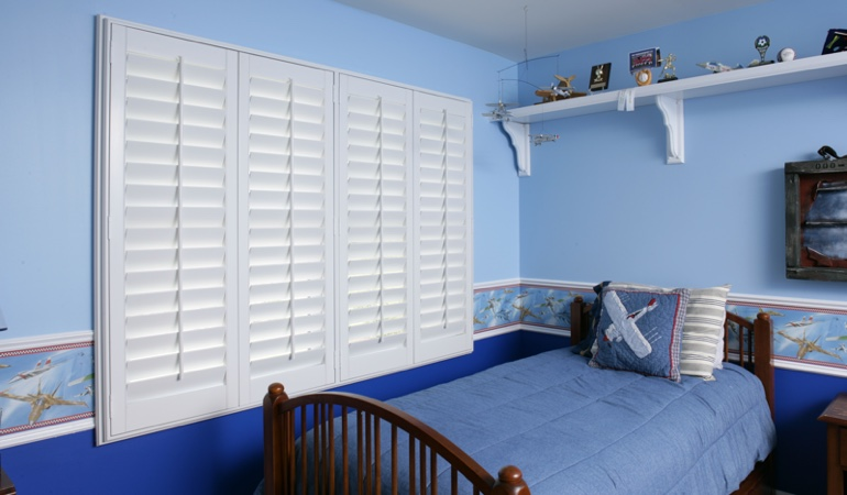 White plantation shutters in blue kids bedroom in Jacksonville